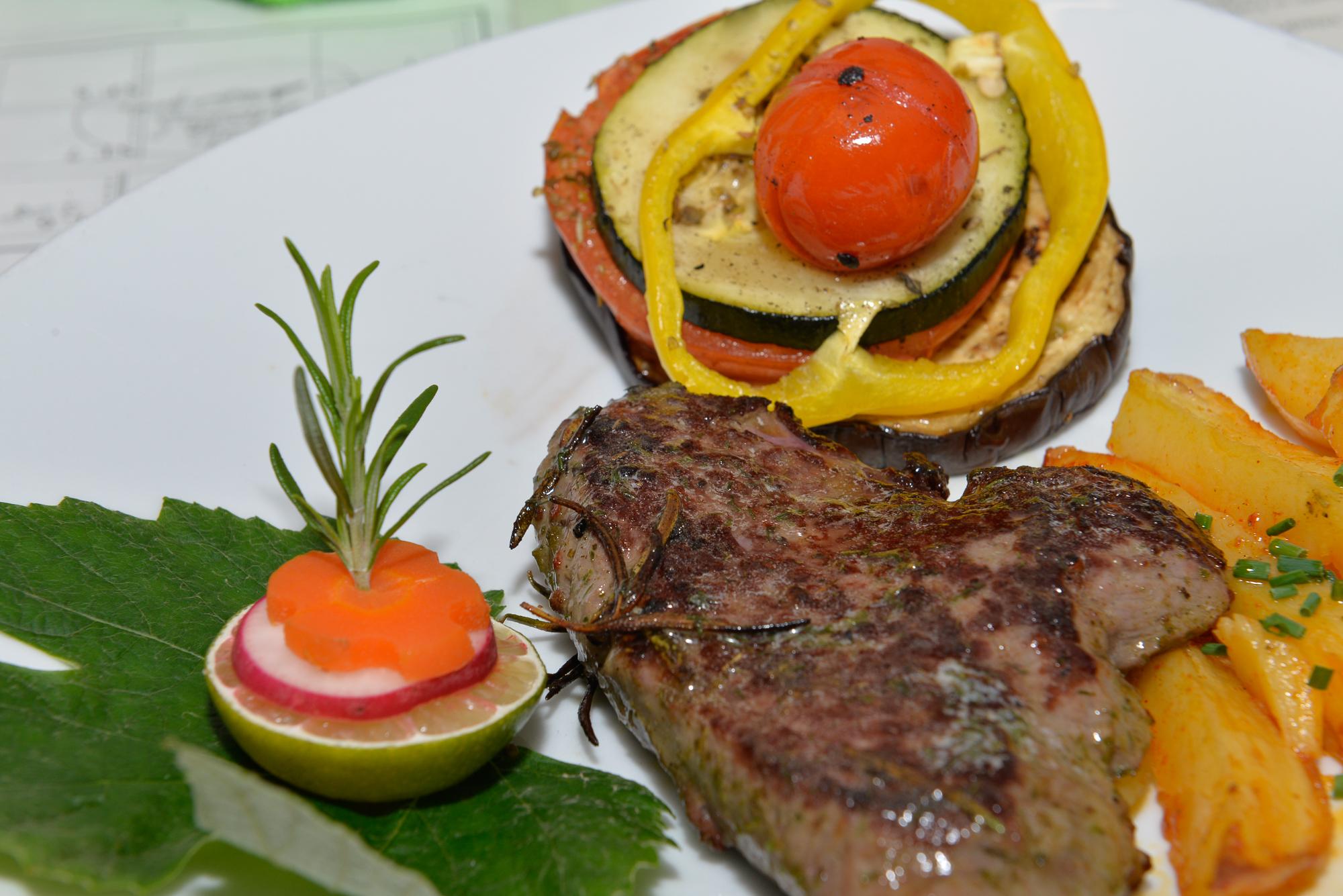 Tourendes von der argentinisches Rinderhüfte auf buntem Grillgemüse und kross gebratenen Kartoffelstiften